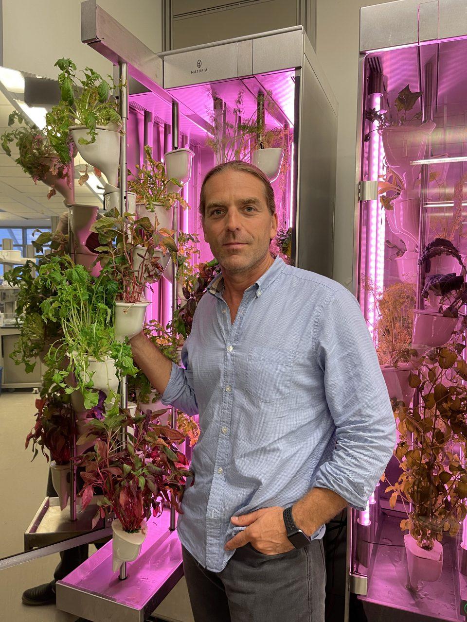 Gregory Lu CEO of Natufia next to the unit with abundant plants