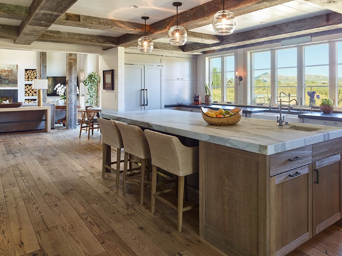 Spacious kitchen with wooden cabinets and marble top island with windows looking outside