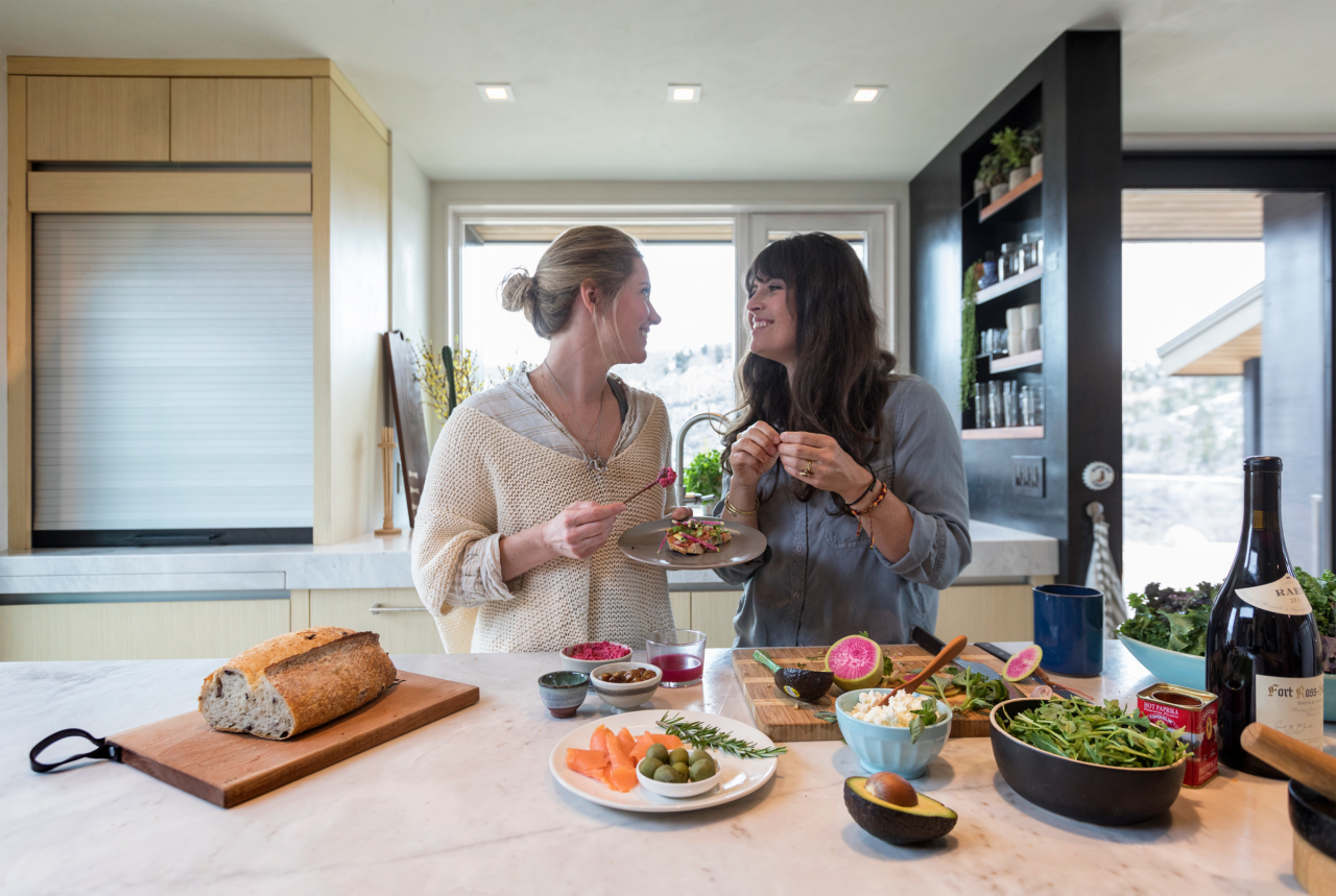 Women in the kitchen looking at each other, eating nad laughing. Food on the table. Wellbeing kitchen with Natufia kitchen garden